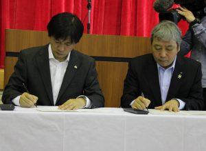 協定書に署名するJA大分中央会二宮伊作会長(右)ら